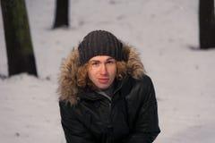 El hombre se sienta en la nieve en el parque Fotos de archivo libres de regalías