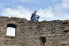 El hombre se sienta en la pared vieja superior del castillo Imágenes de archivo libres de regalías