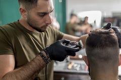 El hombre se sienta en la silla en una peluquería de caballeros El peluquero en guantes negros afeita los pelos del hombre en el  foto de archivo