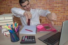 El hombre se sienta en la tabla con un ordenador y los accesorios del negocio Fotografía de archivo