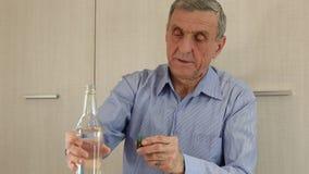 El hombre se sienta en la tabla y bebe la vodka metrajes
