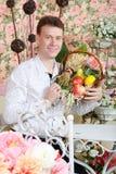 El hombre se sienta en la tabla y sostiene la cesta con la gavilla de trigo Foto de archivo