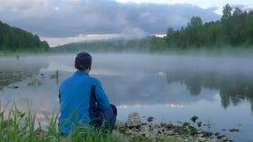 El hombre se sienta en la tierra y las miradas en el flujo tranquilo del río con niebla metrajes