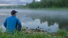 El hombre se sienta en la tierra y las miradas en el flujo tranquilo del río con niebla almacen de video