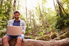 El hombre se sienta en tronco de árbol en Forest Using Laptop Computer imagenes de archivo