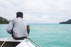 El hombre se sienta en un frente del barco mientras que cruza Andaman Fotos de archivo