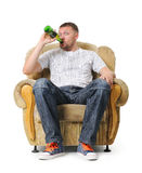 El hombre se sienta en una butaca y bebe la cerveza Fotos de archivo
