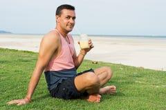 El hombre se sienta en una hierba en el país tropical de la isla Samui, el smoothie de las bebidas del hombre Imagenes de archivo