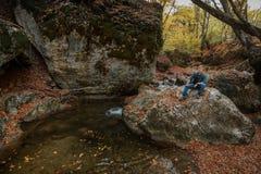 El hombre se sienta en una piedra cerca de una corriente en otoño imagenes de archivo