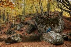 El hombre se sienta en una piedra cerca de una corriente en oto?o imágenes de archivo libres de regalías