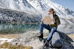 El hombre se sienta en una piedra contra un paisaje de la montaña imagen de archivo