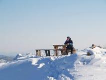 El hombre se sienta en una tabla encima de una montaña imagen de archivo libre de regalías