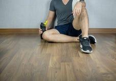 El hombre se sienta y descansa sobre piso del gimnasio con la botella del deporte acuático Fotos de archivo libres de regalías