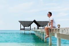 El hombre se sienta y mira fijamente en la distancia en el puente Fotos de archivo libres de regalías