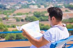 El hombre se sienta y sosteniendo el mapa Fotos de archivo