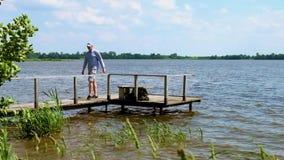 El hombre se va con un embarcadero en el lago en tiempo ventoso metrajes