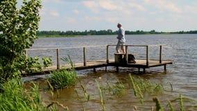 El hombre se va con un embarcadero en el lago en tiempo ventoso almacen de metraje de vídeo