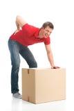 El hombre se vistió en ropa informal dañó su parte posterior que levantaba la caja grande Foto de archivo