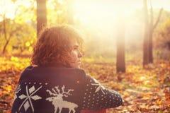 El hombre se vistió en suéter de punto con los ciervos que se sentaban en las hojas de otoño en parque Imagen de archivo libre de regalías