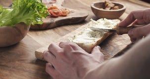 El hombre separó el queso cremoso con las hierbas sobre el baguette en la cámara lenta fotografía de archivo