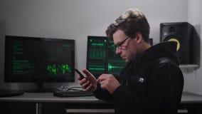 El hombre serio adulto, pareciendo pirata informático, con un pequeño rastrojo en la cara, señala en los ojos, llevando una sudad almacen de video