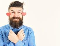 El hombre serio barbudo en camisa azul detiene a pequeñas tarjetas del día de San Valentín de los corazones individuo sonriente h foto de archivo