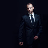 El hombre serio en un traje de negocios, fondo oscuro, hace excursionismo tonos azules imagenes de archivo