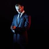 El hombre serio en un traje de negocios, fondo oscuro, hace excursionismo tonos azules y rojos imagenes de archivo