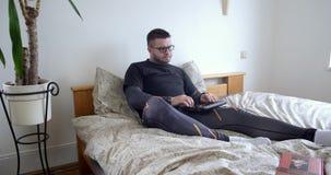 El hombre serio en vidrios acaba de mecanografiar en el ordenador portátil en casa en el dormitorio y el smartphone del uso del c almacen de metraje de vídeo