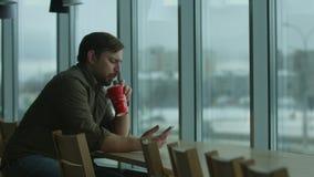 El hombre serio escribe un mensaje y bebidas, por una ventana grande metrajes