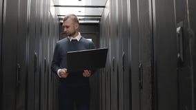El hombre serio que camina y controla los servidores alinea sostener el ordenador portátil almacen de video