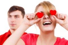 El hombre serio y la mujer loca lleva a cabo corazones rojos sobre ojos Imagenes de archivo