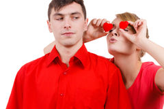 El hombre serio y la mujer loca lleva a cabo corazones rojos sobre ojos Foto de archivo libre de regalías