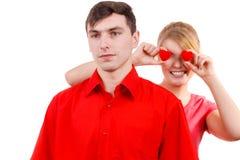 El hombre serio y la mujer loca lleva a cabo corazones rojos sobre ojos Foto de archivo