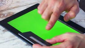 El hombre shoping en línea con la tarjeta de crédito en manos y pantalla verde vacía de la tableta 4K almacen de metraje de vídeo
