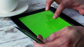 El hombre shoping en línea en café con la pantalla verde vacía de la tableta 4K almacen de metraje de vídeo