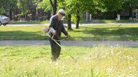 El hombre siega la hierba en ciudad almacen de metraje de vídeo