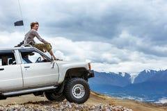 El hombre sienta en el coche SUV la rueda de las montañas Imagen de archivo