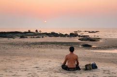 El hombre sienta la posición de loto respecto a la playa del mar en la puesta del sol Foto de archivo libre de regalías