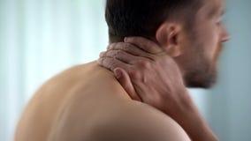 El hombre siente que dolor de cuello después de despertó por la mañana, matrass incómodos, primer imagenes de archivo