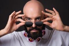 El hombre sin afeitar con el crisantemo florece en la barba y las gafas de sol en fondo oscuro Fotografía de archivo
