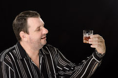 El hombre sin afeitar mira el brandy de cristal Fotografía de archivo