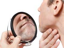 El hombre sin afeitar mira en el espejo foto de archivo