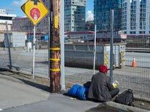 El hombre sin hogar descansa fuera de la estación de Caltrain en San Francisco foto de archivo