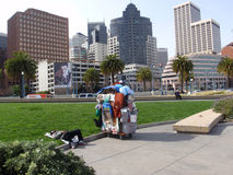 El hombre sin hogar duerme con los carros de la compra hechos en casa llenados del buc Imagen de archivo libre de regalías