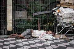 El hombre sin hogar duerme con un carro de la compra Foto de archivo libre de regalías