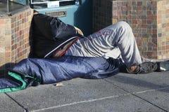 El hombre sin hogar duerme en la calle Imágenes de archivo libres de regalías