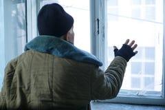 El hombre sin hogar está mirando fuera de la ventana fotos de archivo