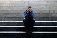 El hombre sin hogar joven perdió el trabajo que se sentaba en la depresión en las escaleras de tierra del hormigón de la calle