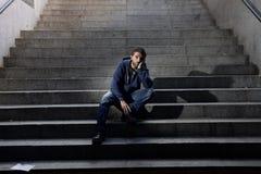 El hombre sin hogar joven perdió en la depresión que se sentaba en las escaleras de tierra del hormigón de la calle foto de archivo libre de regalías